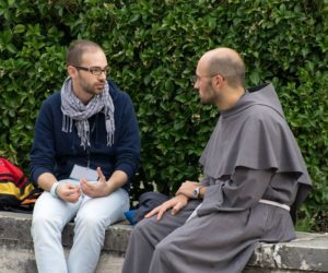 frate parla con un giovane ad Assisi